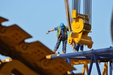 Balance worker guiding a crane (ouvrier en équilibre guidant une grue)