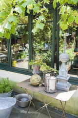 Terrace and reflection in a pane of the house with old iron table and pots surrounded by vineyards and greenery