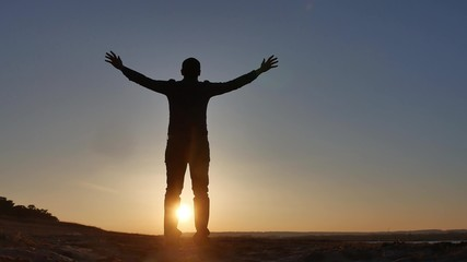 freedom. Man stands on a cliff sunset silhouette hand lifestyle in the sides