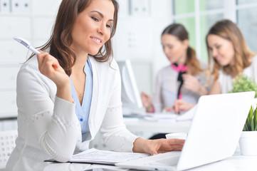 Portrait of a happy business woman using laptop