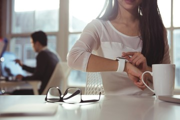 Female executive using smartwatch at desk Wall mural