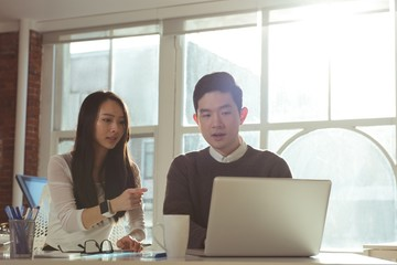 Male and female executives discussing over laptop at desk