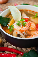 Tom Yum -  Thai Cuisine Delicious King Prawn Soup made with Asian spices: chili, lime, kaffir lemon, coriander, shiitake mushrooms, ginger, Tiger Prawns and garlic.