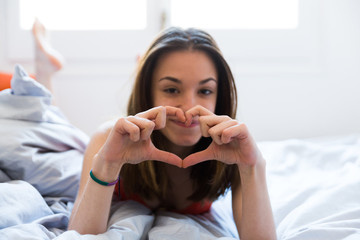 Young girl showing heart in bed