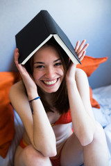 Cheerful girl posing with book