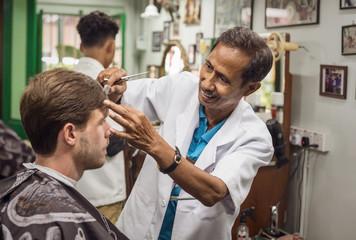 Asiatischer Friseur rasiert Mann