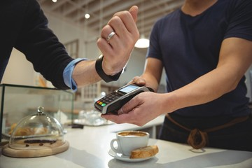 Customer paying with NFC technology on smart watch