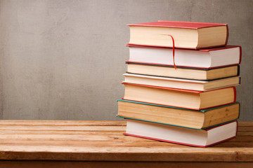 Stack of books on wooden table over rustic background with copy space
