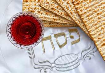 Traditional food (matzah) and drink (red wine) for Jewish Passover Holiday, placed on a white festive serviette with Hebrew word pesah or  Passover