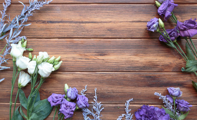 Floral arrangement with eustoma and purple solidago on wooden background, copy space.