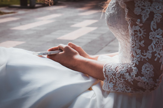Tender bride in white dress with lace is holding phone in her hands. Beauty model girl in wedding day. Hands close-up in the park