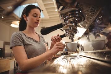 Female barista making espresso in coffee shop