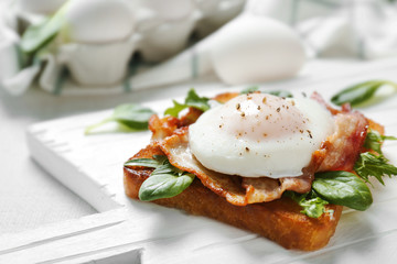 Tasty eggs Benedict on cutting board