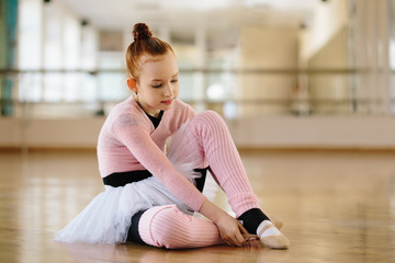 Girl ballerina eating a banana in ballet class