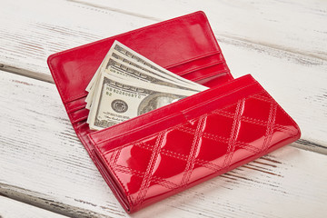 Money in female red leather purse.
