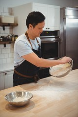 Chef mixing flour in bowl in professional kitchen