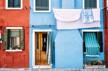 Beautiful Burano island colorful (red and blue) house wall facade