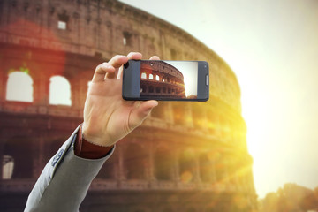 Tourist taking a picture in front of Colosseum at spring sunset, Rome, Italy. Travel concept