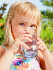 Little girl drinking water  in a summer garden