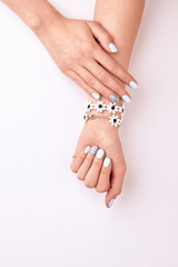 Fototapete - Delicate female hands with a floral bracelet on a white background.