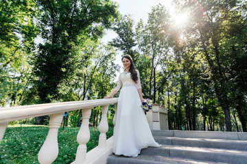 Bride in white wedding dress with bouquet in hand walking down stairs