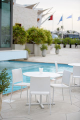 White table with white chairs by the swimming pool at the hotel at beach resort