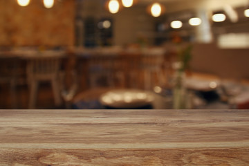 wooden table in front of abstract restaurant lights background