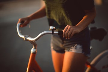 Mid section of woman riding bicycle