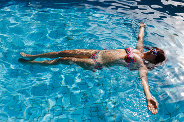 Woman lies in outdoor pool