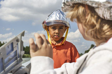 Portrait of boy with self-made helmet playing spaceman with his friend
