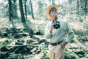 Retired man with hat and camera looking up at trees in forest.