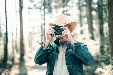 Man with hat and jeans jacket taking picture in forest.