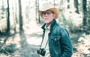 Photographer wearing straw hat and jeans jacket in sunny forest.