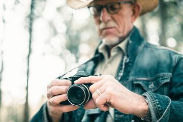 Senior photographer in forest adjusting camera.