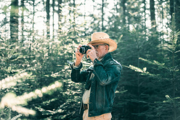 Senior man with hat photographing in pine forest.