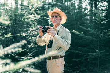 Retired man with camera and binocular in forest.