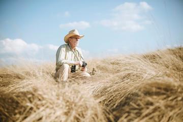 Senior safari man with camera in tall grass.