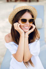 Cute girl in brown sunglasses and straw hat smiles widely and holds her hands near chin. She wears white dress with open shoulders. She sits on a beach chaise-longue.