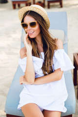 Cute girl in brown sunglasses and straw hat smiles widely and holds her hand near chin. She wears white short dress with open shoulders. She sits on a beach chaise-longue.