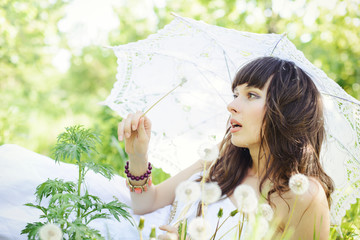 woman with dandelions looks, in a white dress and with a sun umbrella, gentle spring colors, soft contrast. warm cozy photo
