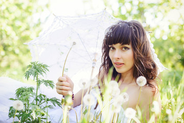 playful look romantic woman with dandelions looking at camera, lying on the grass in a white dress and with a sun umbrella, gentle spring colors, soft contrast. warm cozy photo