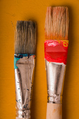 Paint brushes on the yellow background vertical