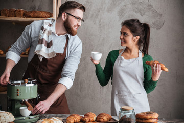 Happy loving couple bakers drinking coffee