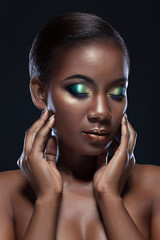 Beautiful African-American girl touching her face with closed eyes, sensual beauty Portrait of a handsome woman on dark background