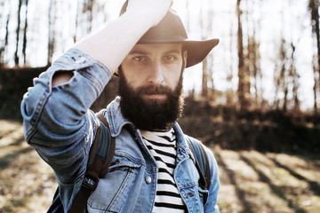 handsome bearded hipster man in a hat and denim jacket in the woods. Street style