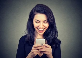 Laughing woman text messaging on smart phone having a pleasant chart conversation