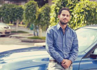 Handsome man standing in front of his car