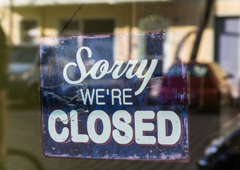Sorry we're closed sign in a shop window