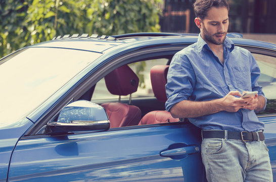 Man standing by his car texting on mobile phone