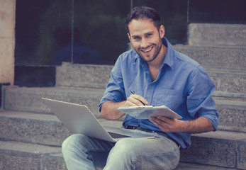 A handsome man sitting on steps with laptop and a notepad